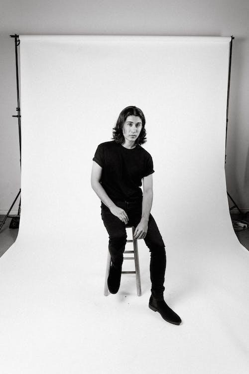 Monochrome Photo of Man Sitting on Stool