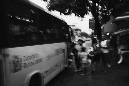 Monochrome Photo of People Getting on the Bus