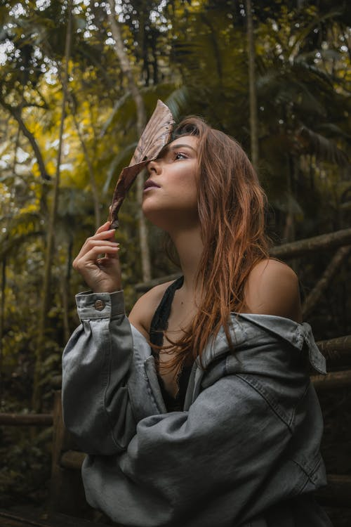 Woman Wearing Denim Jacket While Holding Leaf