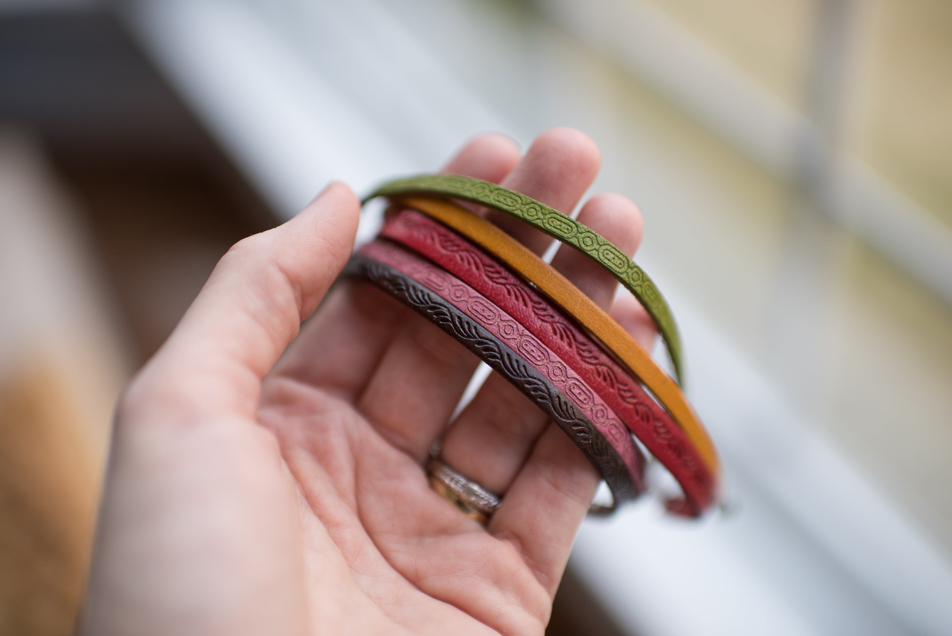 Close-up of Human Hand Holding Multi Colored Bracelets