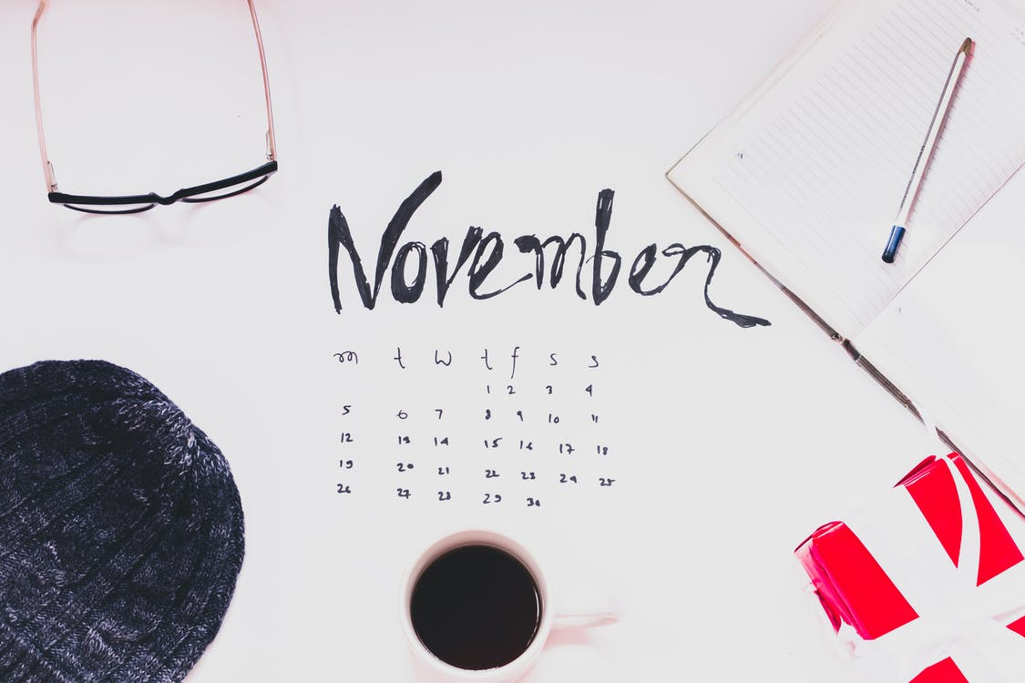 Top View Of A Cup Of Coffee And And Variour Other Items n Top Of The November Month Calender