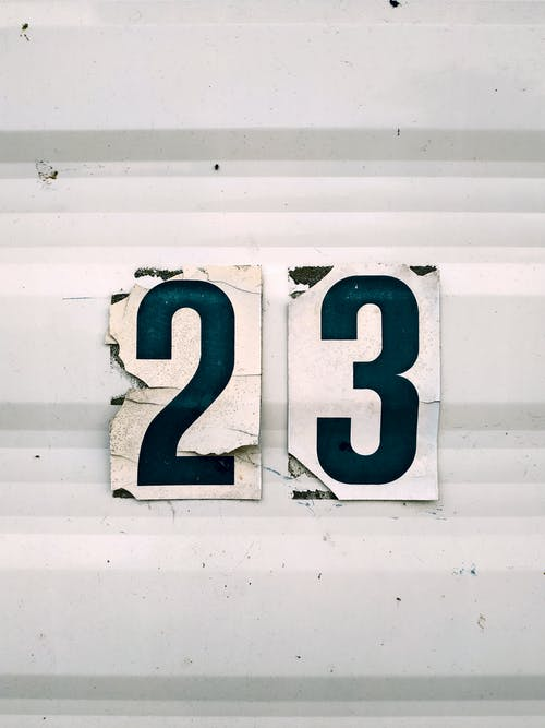 Close-up Of  The Number 23 Sticker On A White Corrugated Surface