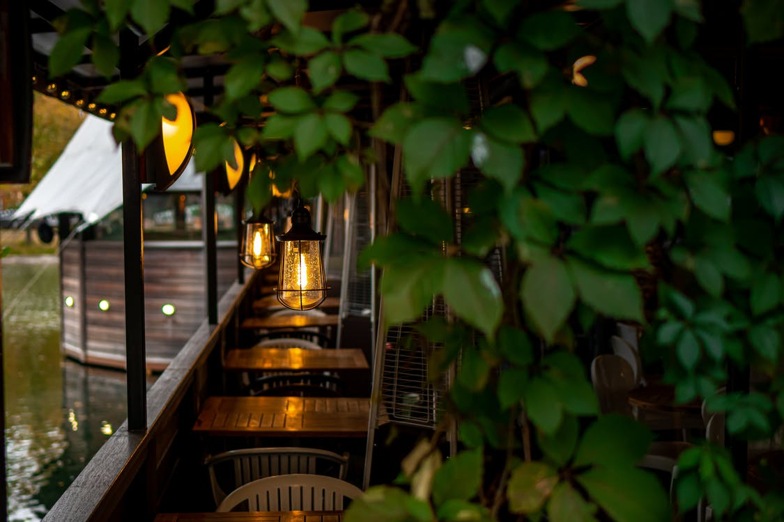 A Row Of Brown Wooden Tables With Pendant Lights In An Establishment By A Calm Body of Water