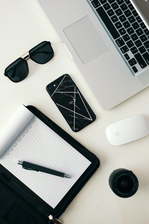 Вид сверху ручки на блокноте, солнцезащитные очки и различные электронные гаджеты на белой столешнице