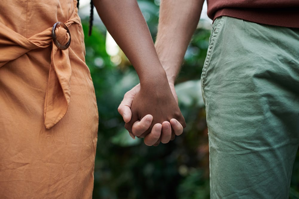 Man and woman holding hands. | Photo: Pexels