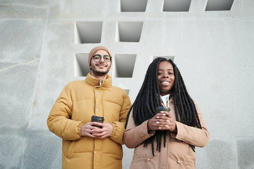 Photo of Two People Holding a Disposable Cup