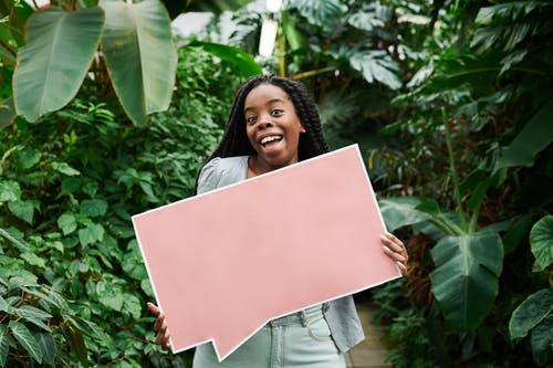 Photo of Woman Smiling While Holding Blank Signboard
