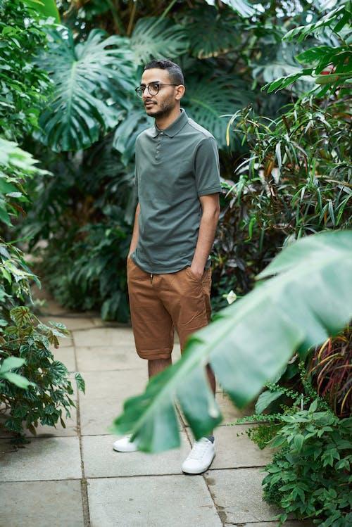 Photo Of Man Standing Beside Plants