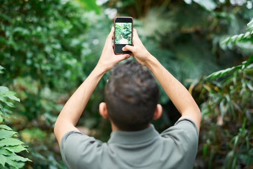 Selective Focus Photo of Man Taking Picture Using Smartphone