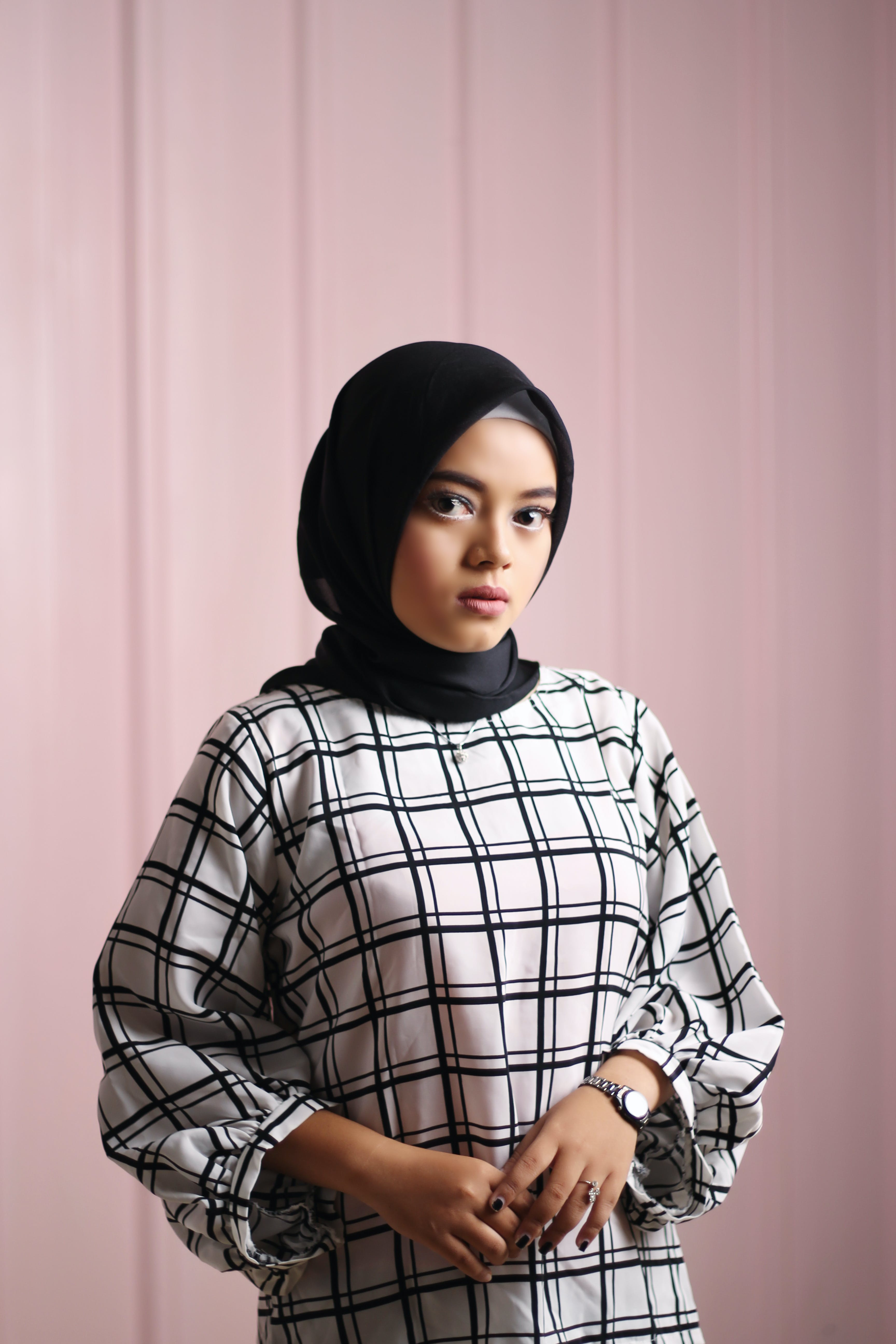 Woman Wearing White and Black Grid Pattern Dress and Black Hijab Standing Near Wall