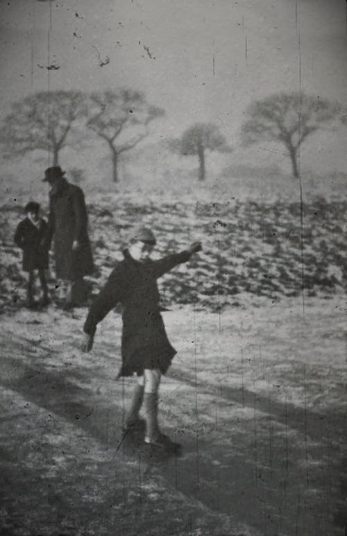A Stained Monochrome Old Photo Of Child Playing With An Adult And A Kid On The Background Outdoor In Winter
