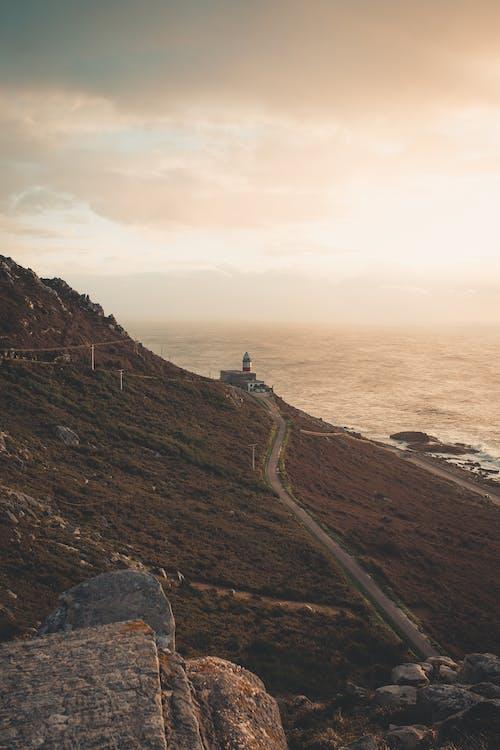 Gratis arkivbilde med bølger, fjell, fyr
