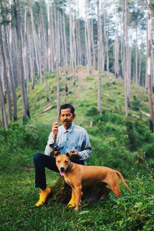 Photo Of Man Sitting Beside Dog