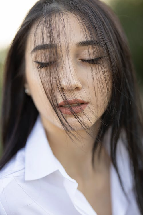 Woman in White Dress Shirt Closing Her Eyes