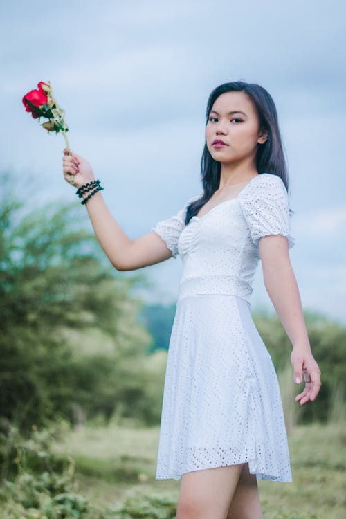 Woman Wearing White Dress While Holding a Rose