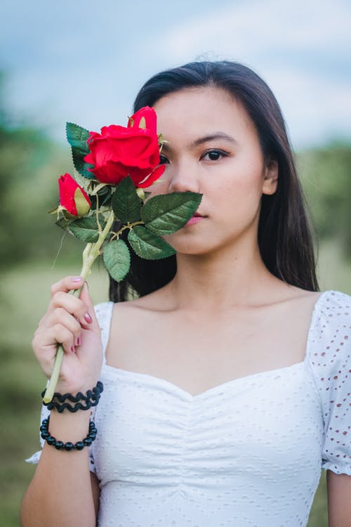 Photo of Woman Holding a Rose