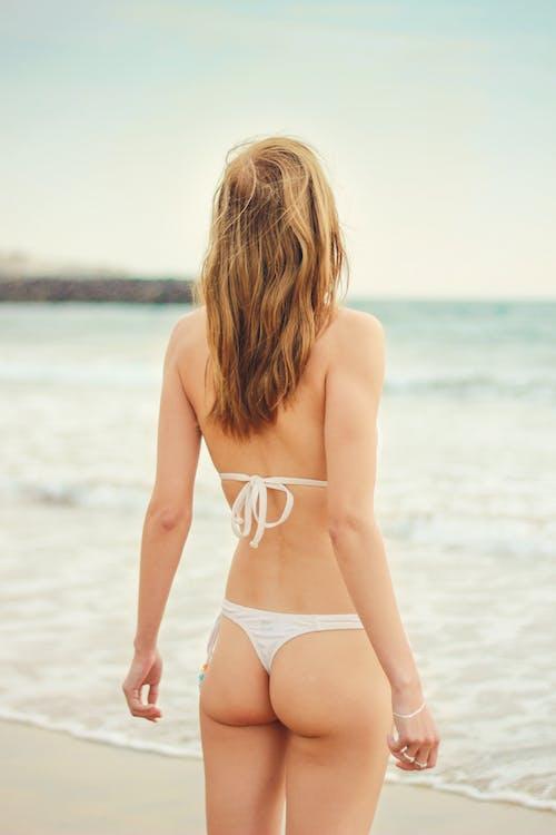 Donna In Bikini Bianco In Piedi Vicino Al Mare