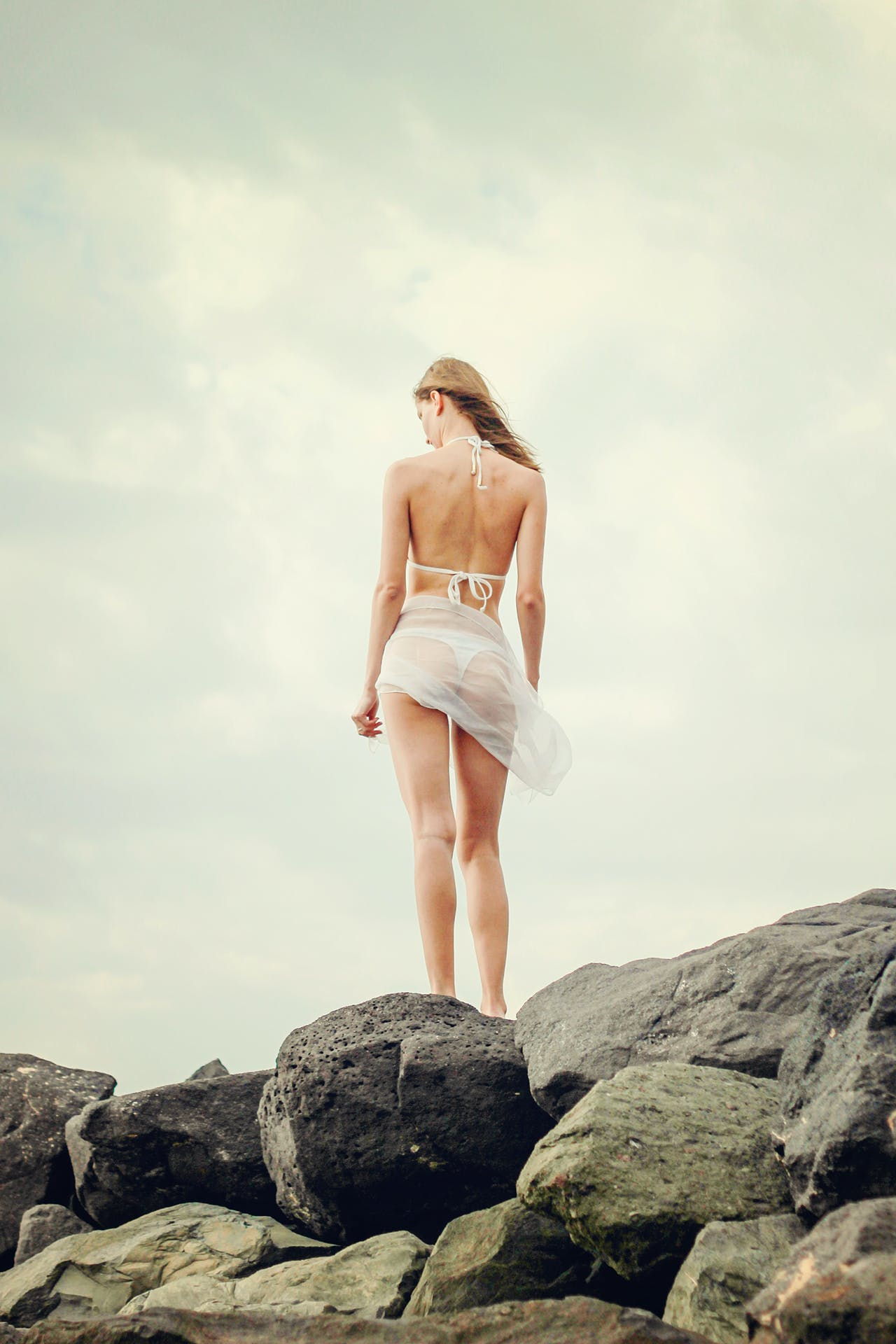 Young Woman Standing on Rock Against Sky