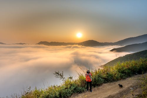 Person Wearing Red Backpack Facing Sea of Clouds