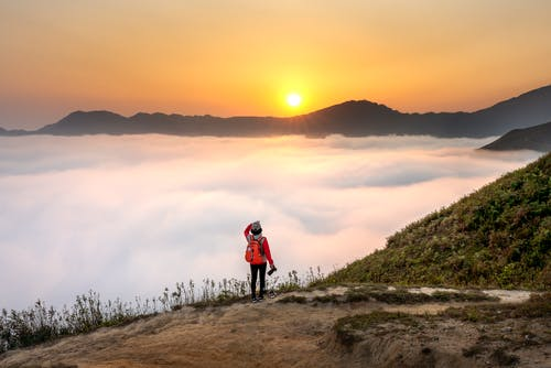 Person Carrying Red Backpack Facing Sea of Clouds