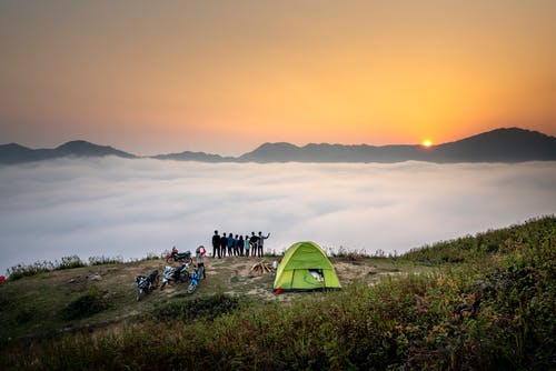 People Standing on Cliff Looking at Sea of Clouds