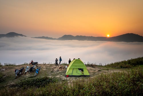 People Standing Near Camping Tent Overlooking Sea of Clouds during Golden Hour