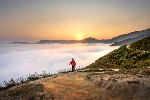 Person Standing Overlooking Sea of Clouds