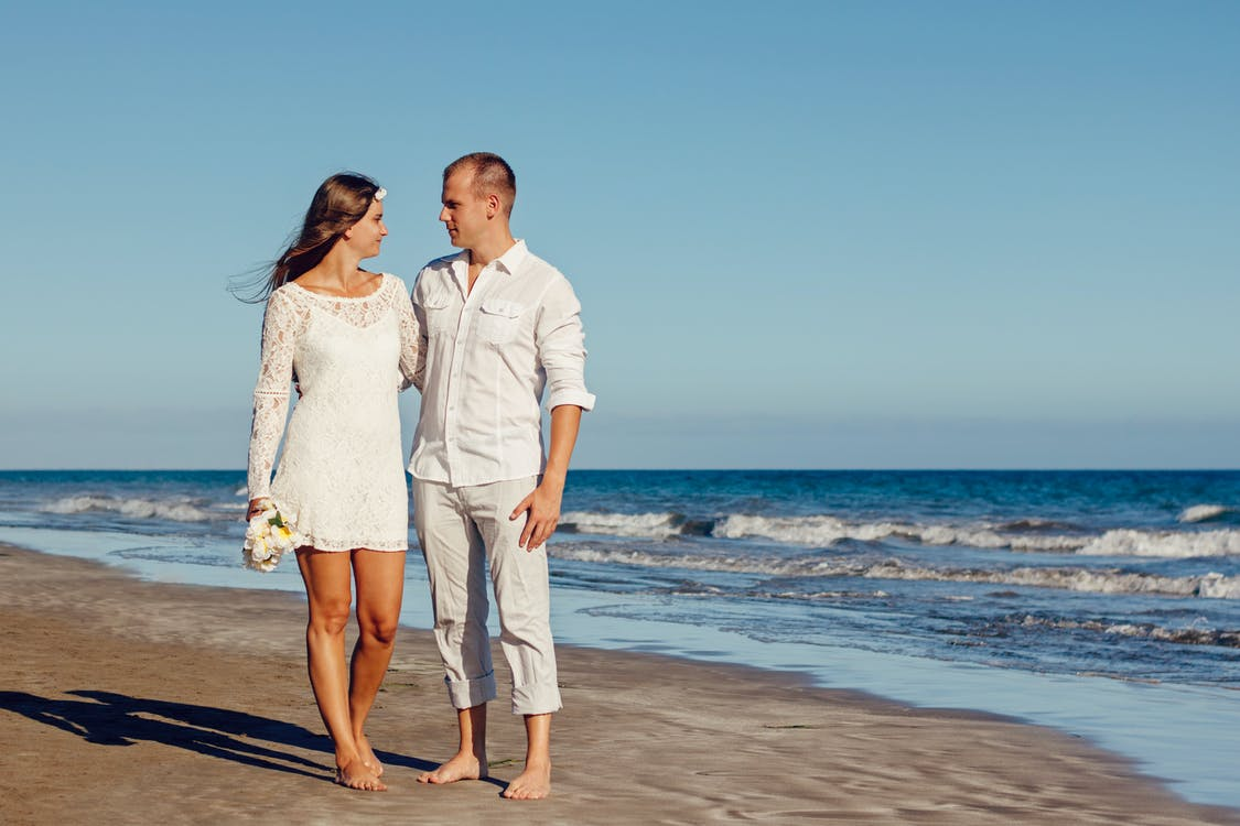 Man and Woman Standing Beside Each Other on Seashore