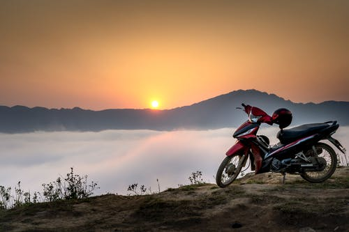 Red and Black Underbone Motorcycle on Mountain Cliff Surrounded by Sea of Clouds