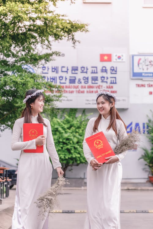 Two Smiling Women Wearing White Dress Holding Books