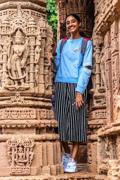 Woman Standing Beside Brown Statue