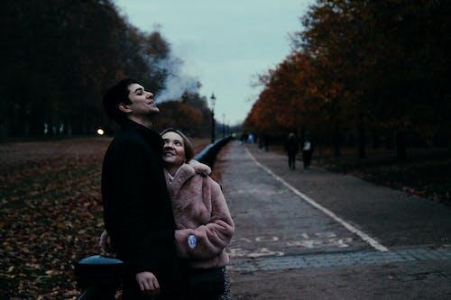 Darmowe zdjęcie z galerii z dymiący, para, przytulanie się pary, spacerująca para