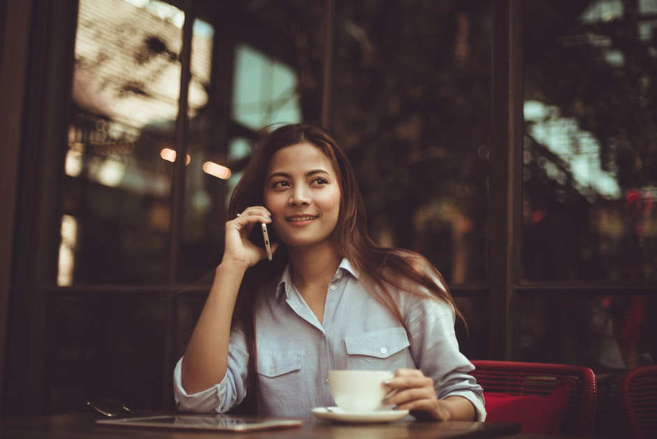 Portrait of Young Woman Using Mobile Phone in Cafe