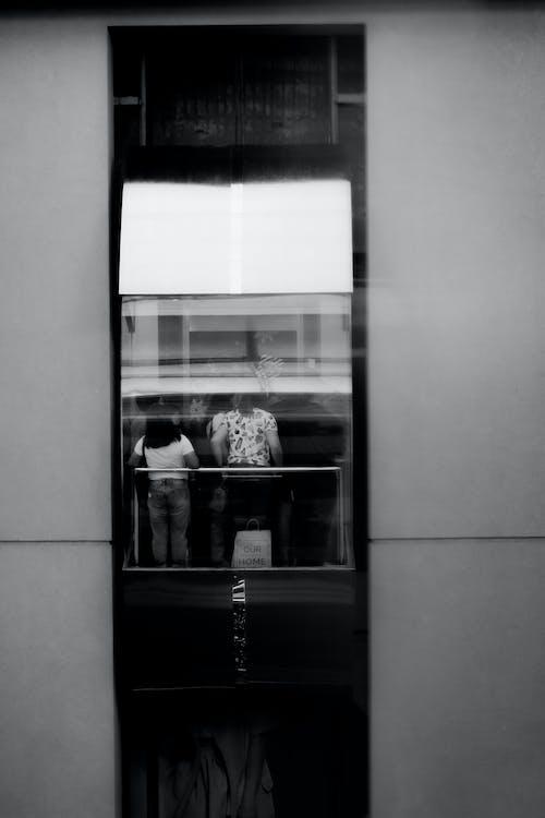 電梯裡的人的灰度攝影