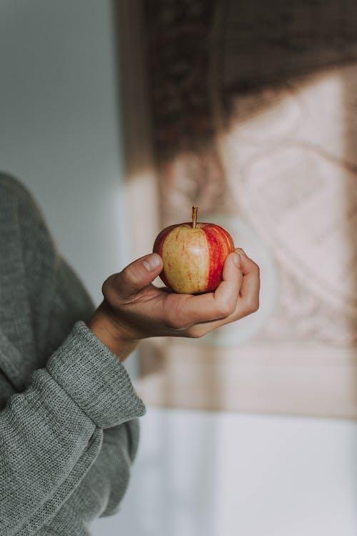 Selective Focus Photo Holding Apple Fruit