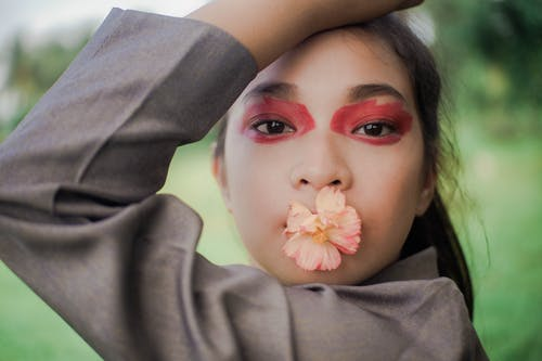 Close-up Photo of Woman with Flower on Her Mouth