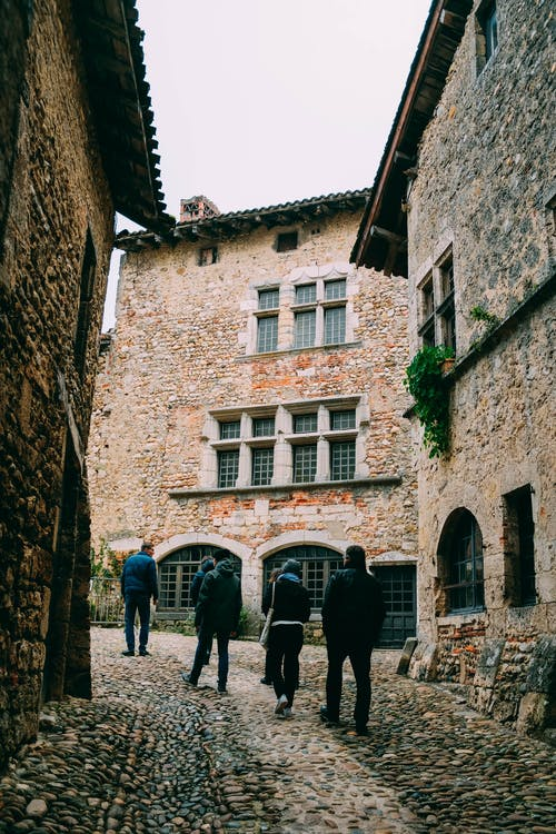 People Walking in Between Stone Walled Buildings Along A Narrow Cobblestone Alley
