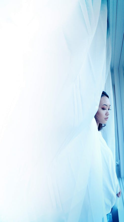 Woman Standing Beside White Curtain