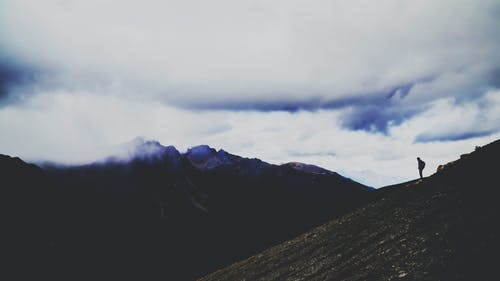 Silhouette Photo of Person Standing on Mountain