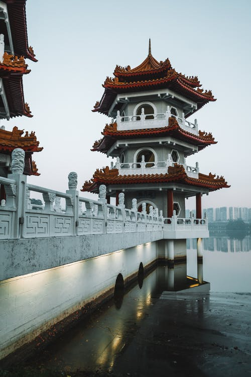 White and Maroon Temple Near Body of Water