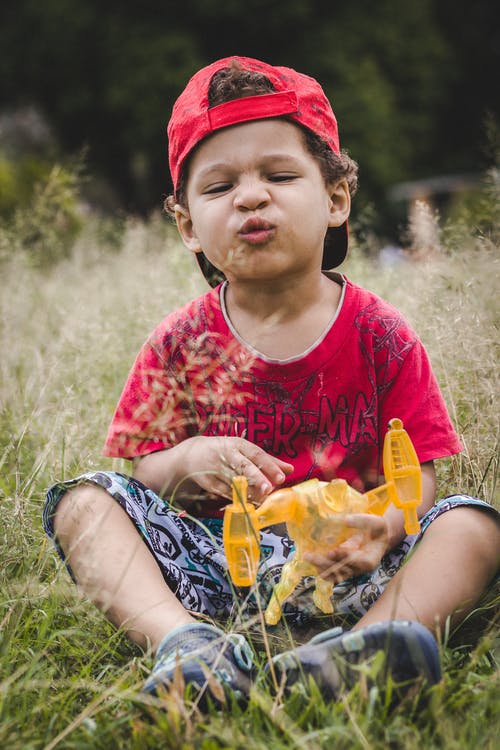 Photo Of Boy Sitting On Grass