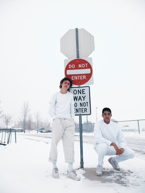 Two Men in White Sweaters Standing and Crouching Beside Road Sign