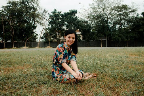 Smiling Woman Sitting on Grass Field