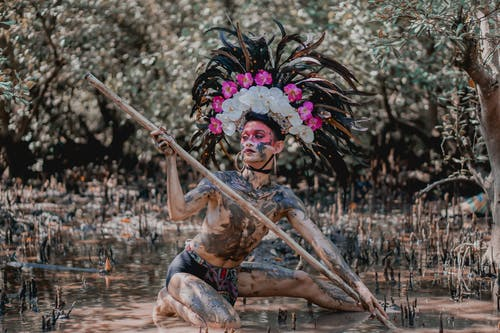 Person Wearing Feather Headdress Holding Wooden Stick While Kneeling on Mud