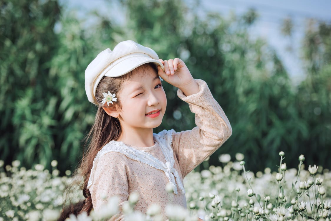 Selective Focus Photography of Girl Wearing Cap Standing Beside Flowers