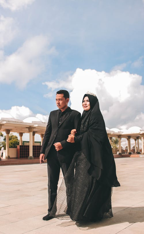 Woman Wearing Black Hijab Holding Man in Black Suit