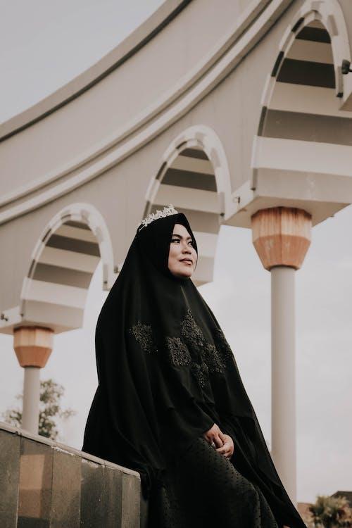 Женщина в хиджабе сидит