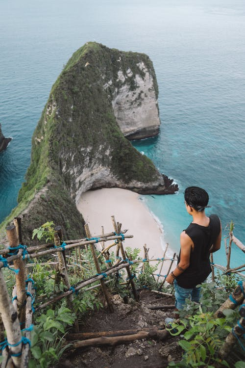 Photo of a Man in Black Tank Top Looking at the Beautiful Paradise