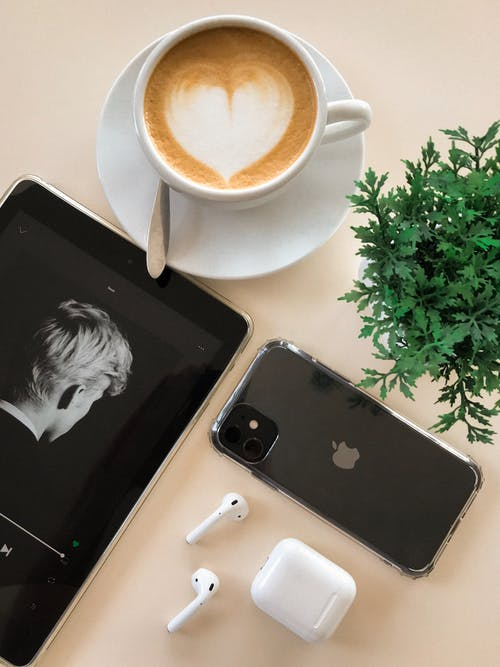 Black Iphone 11 Beside Airpods and Coffee Cup