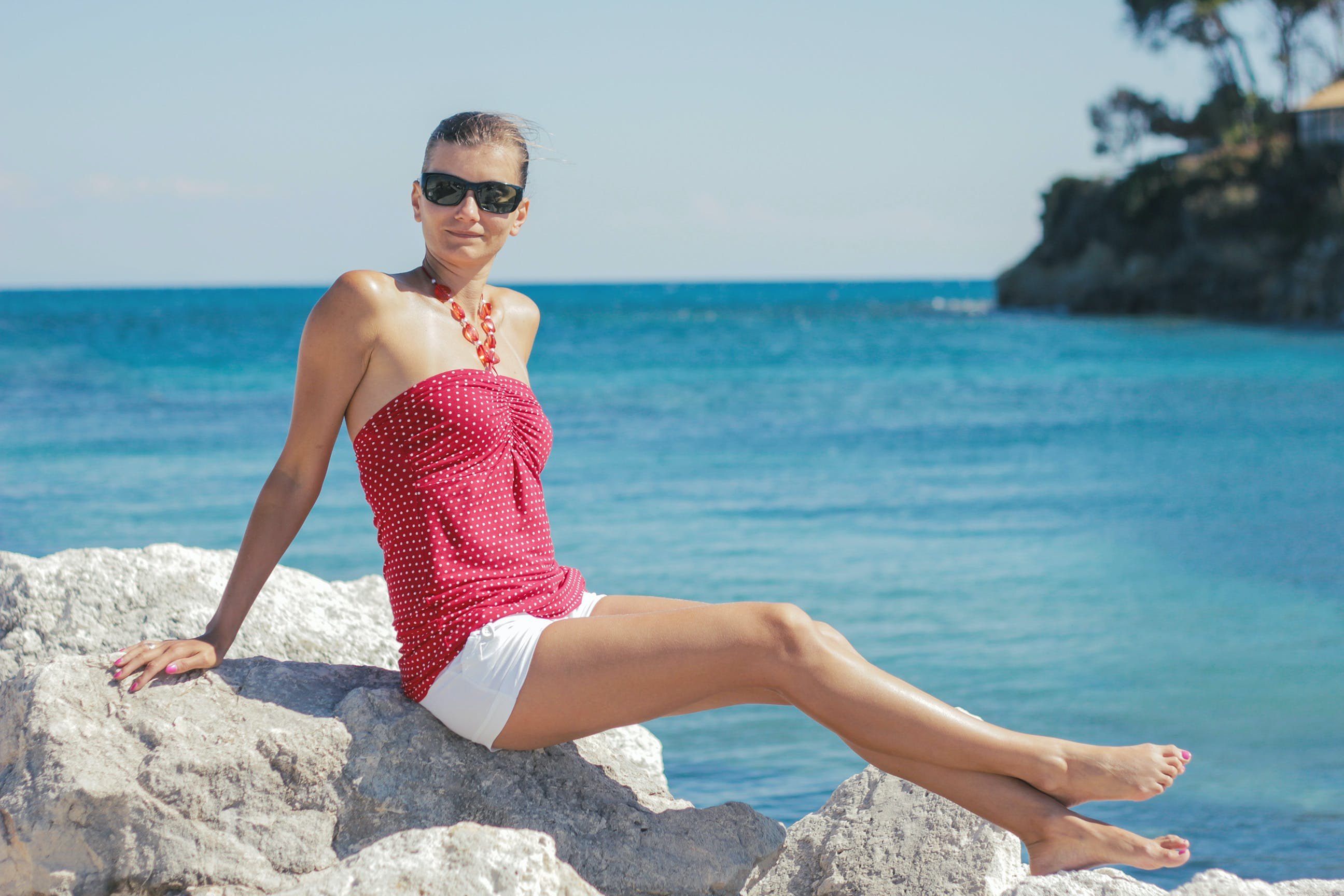 Woman Wearing Pink Tube Top Sitting on Rock